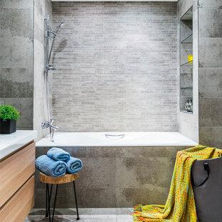 Удачное сочетание для дизайна помещения: главная ванная комната в современном стиле с плоскими фасадами, фасадами цвета светлого дерева, ванной в нише, душем над ванной, серой плиткой, монолитной раковиной и серым полом - самое интересное для вас