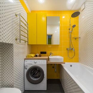 На фото: главная ванная комната в современном стиле с душем над ванной, инсталляцией, белой плиткой, желтой плиткой, настольной раковиной, столешницей из дерева, серым полом, открытым душем, коричневой столешницей, открытыми фасадами и ванной в нише с