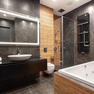 Пример оригинального дизайна: ванная комната в современном стиле с плоскими фасадами, черными фасадами, накладной ванной, угловым душем, инсталляцией, черной плиткой, черными стенами, настольной раковиной, черным полом, душем с распашными дверями и черной столешницей