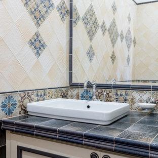 Пример оригинального дизайна: ванная комната в классическом стиле с фасадами с утопленной филенкой, белыми фасадами, накладной раковиной, столешницей из плитки и синей столешницей