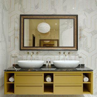 Immagine di una stanza da bagno padronale tradizionale con ante lisce, ante gialle, piastrelle bianche, piastrelle grigie, lavabo a bacinella, pavimento bianco, top nero, vasca freestanding, piastrelle di marmo, pareti bianche, pavimento con piastrelle a mosaico e top in marmo