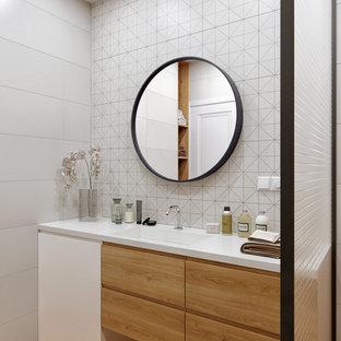 Diseño de cuarto de baño contemporáneo, pequeño, con armarios con paneles lisos, puertas de armario de madera clara, baldosas y/o azulejos blancos, baldosas y/o azulejos de porcelana, paredes blancas, encimera de acrílico, suelo beige, encimeras blancas y lavabo integrado