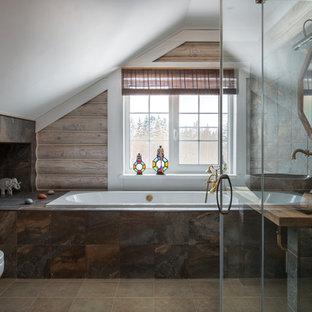 На фото: главная ванная комната в стиле рустика с накладной ванной, инсталляцией, коричневой плиткой, коричневыми стенами, настольной раковиной, столешницей из дерева, бежевым полом и коричневой столешницей с