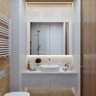 Идея дизайна: ванная комната среднего размера в современном стиле с фасадами с филенкой типа жалюзи, белыми фасадами, инсталляцией, белой плиткой, керамической плиткой, белыми стенами, полом из керамогранита, душевой кабиной, столешницей из искусственного камня, серым полом, белой столешницей и настольной раковиной