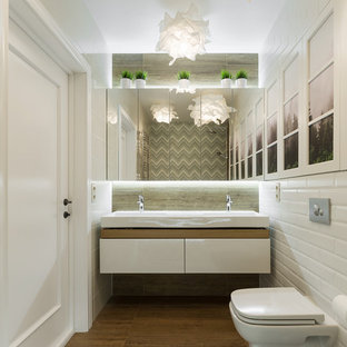 Пример оригинального дизайна: ванная комната в современном стиле с инсталляцией, полом из керамогранита, плоскими фасадами, белыми фасадами, душем в нише, серой плиткой, белой плиткой, плиткой кабанчик, душевой кабиной, монолитной раковиной и коричневым полом