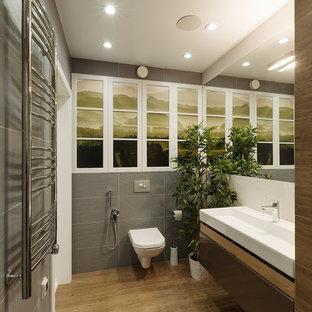 Modernes Badezimmer mit Schrankfronten mit vertiefter Füllung, Wandtoilette, Porzellan-Bodenfliesen, braunen Schränken, grauen Fliesen, integriertem Waschbecken, braunem Boden und weißer Waschtischplatte in Jekaterinburg