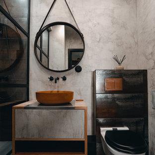 На фото: ванная комната в стиле лофт с серыми стенами, душевой кабиной, настольной раковиной и серым полом с