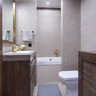 Пример оригинального дизайна интерьера: главная ванная комната в современном стиле с плоскими фасадами, темными деревянными фасадами, ванной в нише, душем над ванной, раздельным унитазом, серой плиткой и накладной раковиной