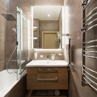 モスクワの中くらいのコンテンポラリースタイルのおしゃれなマスターバスルーム (フラットパネル扉のキャビネット、中間色木目調キャビネット、アルコーブ型浴槽、シャワー付き浴槽、茶色いタイル、磁器タイル、茶色い壁、磁器タイルの床、一体型シンク、人工大理石カウンター、茶色い床、引戸のシャワー、白い洗面カウンター) の写真