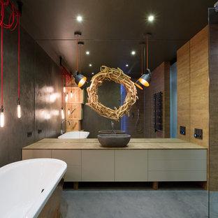 Modelo de cuarto de baño industrial con lavabo sobreencimera, armarios con paneles lisos, puertas de armario beige, bañera exenta, ducha a ras de suelo y paredes grises