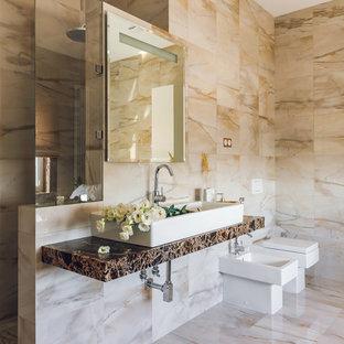 Создайте стильный интерьер: ванная комната в современном стиле с биде, бежевой плиткой, душевой кабиной, настольной раковиной, бежевым полом, душем в нише, бежевыми стенами и открытым душем - последний тренд