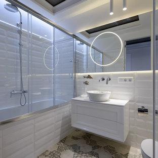 Свежая идея для дизайна: главная ванная комната в современном стиле с настольной раковиной, фасадами с утопленной филенкой, белыми фасадами, ванной в нише, душем над ванной, белой плиткой, белыми стенами, серым полом и душем с раздвижными дверями - отличное фото интерьера