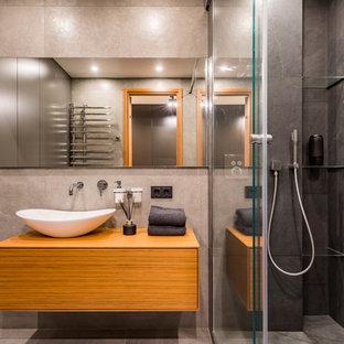 На фото: ванная комната в современном стиле с плоскими фасадами, фасадами цвета дерева среднего тона, серой плиткой, душевой кабиной, настольной раковиной, серым полом, душем в нише, серыми стенами, столешницей из дерева и душем с раздвижными дверями с
