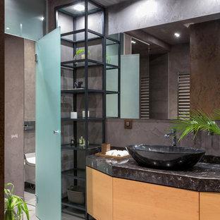 На фото: ванная комната в стиле лофт с плоскими фасадами, фасадами цвета дерева среднего тона, настольной раковиной, серым полом, черной столешницей и серыми стенами с