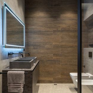 Industriell inredning av ett grå grått badrum, med släta luckor, grå skåp, ett urinoar, brun kakel, ett fristående handfat och beiget golv