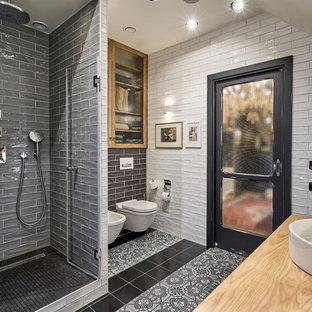 Пример оригинального дизайна: ванная комната среднего размера в стиле лофт с белой плиткой, серой плиткой, душевой кабиной, душем в нише, настольной раковиной, столешницей из дерева, разноцветным полом и душем с распашными дверями