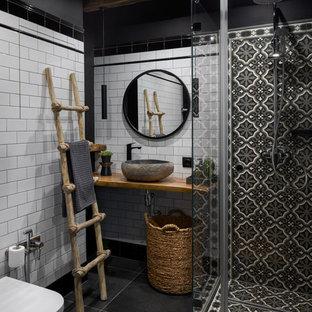 Inredning av ett industriellt litet brun brunt badrum med dusch, med en vägghängd toalettstol, svart och vit kakel, vit kakel, svarta väggar, klinkergolv i porslin, träbänkskiva, svart golv och ett fristående handfat