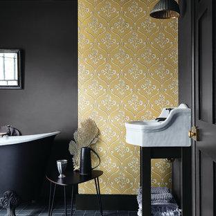 Идея дизайна: главная ванная комната в стиле современная классика с ванной на ножках, желтыми стенами, консольной раковиной и черным полом