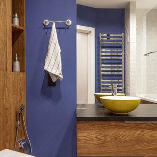 На фото: ванная комната в современном стиле с плоскими фасадами, фасадами цвета дерева среднего тона, фиолетовыми стенами, разноцветным полом и черной столешницей с