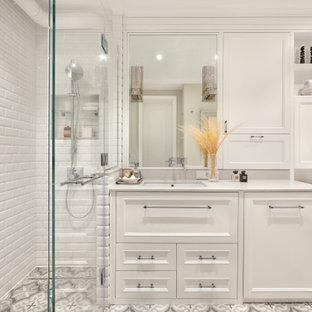 На фото: ванная комната в стиле современная классика с фасадами с утопленной филенкой, белыми фасадами, полновстраиваемой ванной, белой плиткой, врезной раковиной, серым полом, белой столешницей, нишей, тумбой под одну раковину и встроенной тумбой с