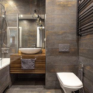 Удачное сочетание для дизайна помещения: ванная комната в современном стиле с плоскими фасадами, темными деревянными фасадами, инсталляцией, серой плиткой, серым полом, коричневой столешницей, ванной в нише, душем над ванной, душевой кабиной, настольной раковиной, столешницей из дерева и открытым душем - самое интересное для вас
