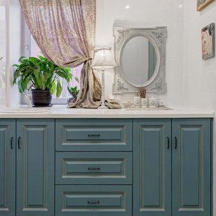 Свежая идея для дизайна: ванная комната в современном стиле с фасадами с выступающей филенкой, синими фасадами, белой плиткой, накладной раковиной и белой столешницей - отличное фото интерьера