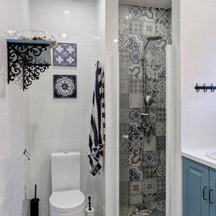 Неиссякаемый источник вдохновения для домашнего уюта: ванная комната в современном стиле с фасадами с выступающей филенкой, синими фасадами, угловым душем, раздельным унитазом, белой плиткой, душевой кабиной, накладной раковиной, серым полом, душем с распашными дверями и белой столешницей
