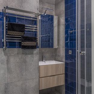 На фото: ванная комната в современном стиле с плоскими фасадами, светлыми деревянными фасадами, синей плиткой, серой плиткой, душевой кабиной, монолитной раковиной и серым полом с