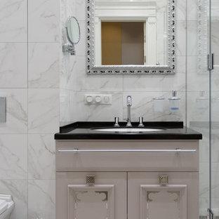 Стильный дизайн: ванная комната в стиле современная классика с белой плиткой, душевой кабиной, врезной раковиной, белым полом, угловым душем, белыми стенами и душем с распашными дверями - последний тренд