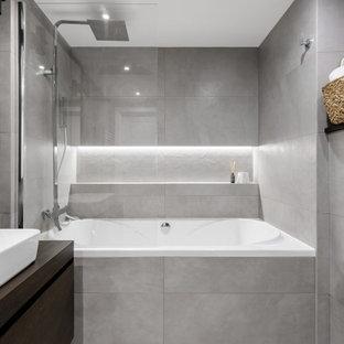 Идея дизайна: ванная комната среднего размера в современном стиле с плоскими фасадами, темными деревянными фасадами, ванной в нише, угловым душем, инсталляцией, серой плиткой, керамогранитной плиткой, серыми стенами, полом из керамогранита, душевой кабиной, накладной раковиной, столешницей из дерева, серым полом, коричневой столешницей, унитазом, тумбой под одну раковину, подвесной тумбой и душем с распашными дверями
