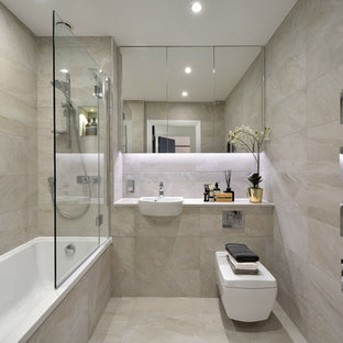 Photo of a contemporary shower room in London with a shower/bath combination, grey tiles, a built-in sink, grey floors and an open shower.