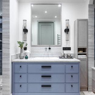 На фото: главная ванная комната среднего размера в современном стиле с фасадами с утопленной филенкой, синими фасадами, белыми стенами, полом из цементной плитки, накладной раковиной, мраморной столешницей, белым полом, серой столешницей и серой плиткой