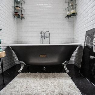 На фото: главная ванная комната в стиле современная классика с ванной на ножках, белой плиткой, плиткой кабанчик и черным полом