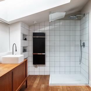 Стильный дизайн: ванная комната среднего размера в современном стиле с фасадами островного типа, коричневыми фасадами, угловым душем, белой плиткой, белыми стенами, паркетным полом среднего тона, душевой кабиной, накладной раковиной, столешницей из дерева, бежевым полом и коричневой столешницей - последний тренд