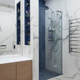 Пример оригинального дизайна: ванная комната среднего размера в современном стиле с плоскими фасадами, светлыми деревянными фасадами, душем в нише, серой плиткой, керамогранитной плиткой, полом из керамогранита, душевой кабиной, монолитной раковиной, серым полом, душем с распашными дверями, белой столешницей, тумбой под одну раковину и подвесной тумбой