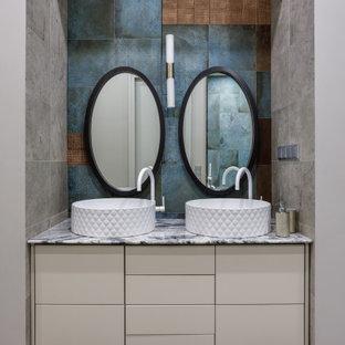 На фото: ванная комната в современном стиле с плоскими фасадами, бежевыми фасадами, синей плиткой, коричневой плиткой, серой плиткой, разноцветной плиткой, разноцветными стенами, настольной раковиной, разноцветным полом, разноцветной столешницей, тумбой под две раковины и подвесной тумбой с
