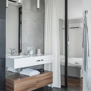 Пример оригинального дизайна: ванная комната в современном стиле с плоскими фасадами, фасадами цвета дерева среднего тона, серой плиткой, черным полом, белой столешницей и монолитной раковиной