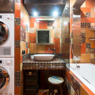 На фото: маленькая главная ванная комната в стиле фьюжн с коричневыми фасадами, душем над ванной, разноцветной плиткой, оранжевой плиткой, керамогранитной плиткой, полом из керамогранита, столешницей из плитки, разноцветным полом, шторкой для душа, ванной в нише, настольной раковиной и разноцветной столешницей с