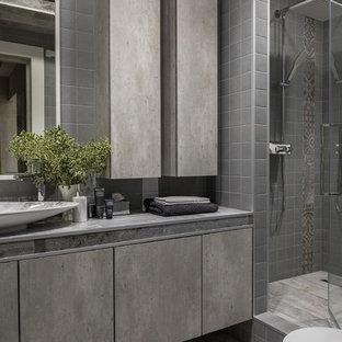 Стильный дизайн: ванная комната в современном стиле с плоскими фасадами, серыми фасадами, душем в нише, серой плиткой, душевой кабиной, настольной раковиной, серым полом, душем с распашными дверями и серой столешницей - последний тренд