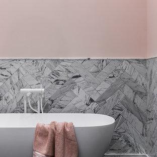 На фото: главные ванные комнаты в современном стиле с отдельно стоящей ванной, розовыми стенами, черным полом и серой плиткой
