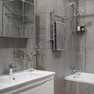 Идея дизайна: главная ванная комната среднего размера в скандинавском стиле с белыми фасадами, ванной в нише, серой плиткой, керамогранитной плиткой, серым полом, плоскими фасадами, душем над ванной, монолитной раковиной, шторкой для ванной, тумбой под одну раковину и подвесной тумбой