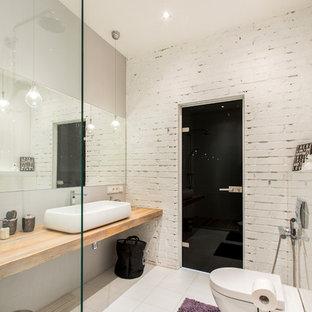 На фото: доступные главные ванные комнаты среднего размера в стиле лофт с инсталляцией, белой плиткой, керамогранитной плиткой, белыми стенами, полом из керамогранита, столешницей из дерева, настольной раковиной, открытым душем и коричневой столешницей