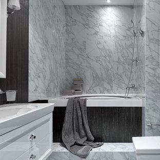 На фото: главная ванная комната в современном стиле с плоскими фасадами, белыми фасадами, полновстраиваемой ванной, душем над ванной, серой плиткой, мраморной плиткой, мраморным полом, монолитной раковиной и серым полом