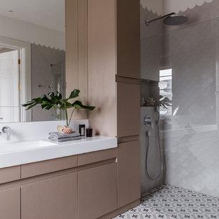 Идея дизайна: ванная комната в современном стиле с плоскими фасадами, бежевыми фасадами, белой плиткой, душевой кабиной, монолитной раковиной, серым полом и белой столешницей