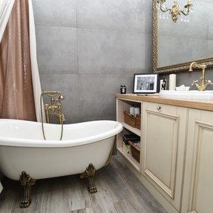 Стильный дизайн: главная ванная комната в стиле лофт с фасадами с выступающей филенкой, бежевыми фасадами, ванной на ножках, душем над ванной, инсталляцией, серой плиткой, керамогранитной плиткой, серыми стенами, полом из керамической плитки, врезной раковиной, столешницей из дерева, серым полом и бежевой столешницей - последний тренд