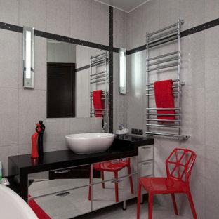 Свежая идея для дизайна: ванная комната среднего размера в современном стиле с плоскими фасадами, отдельно стоящей ванной, серой плиткой, керамогранитной плиткой, полом из керамогранита, душевой кабиной, настольной раковиной, стеклянной столешницей, серым полом и черной столешницей - отличное фото интерьера