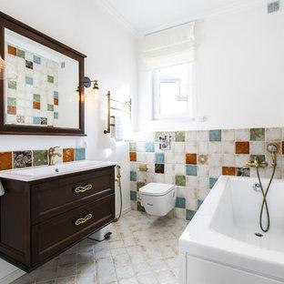 Выдающиеся фото от архитекторов и дизайнеров интерьера: ванная комната в средиземноморском стиле с фасадами с утопленной филенкой, темными деревянными фасадами, угловой ванной, душем над ванной, унитазом-моноблоком, разноцветной плиткой, керамической плиткой, белыми стенами, полом из керамической плитки, душевой кабиной, монолитной раковиной, бежевым полом, открытым душем и белой столешницей