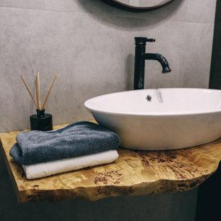 他の地域の中くらいのインダストリアルスタイルのおしゃれなマスターバスルーム (アルコーブ型浴槽、オープン型シャワー、壁掛け式トイレ、グレーのタイル、磁器タイル、グレーの壁、磁器タイルの床、オーバーカウンターシンク、木製洗面台、マルチカラーの床、オープンシャワー、黄色い洗面カウンター、洗面台1つ、フローティング洗面台) の写真