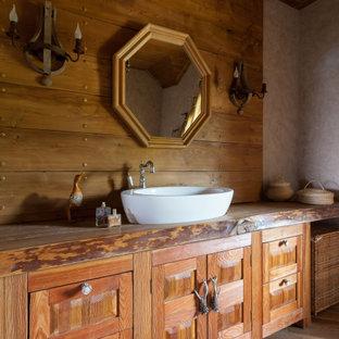 Bild på ett rustikt brun brunt badrum, med luckor med upphöjd panel, skåp i mellenmörkt trä, bruna väggar, mellanmörkt trägolv, ett fristående handfat, träbänkskiva och brunt golv