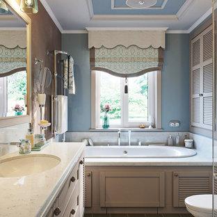 На фото: со средним бюджетом главные ванные комнаты среднего размера в стиле кантри с фасадами с филенкой типа жалюзи, накладной ванной, инсталляцией, синей плиткой, керамической плиткой, синими стенами, полом из керамической плитки, врезной раковиной, мраморной столешницей, коричневым полом, душем с распашными дверями, бежевой столешницей и бежевыми фасадами